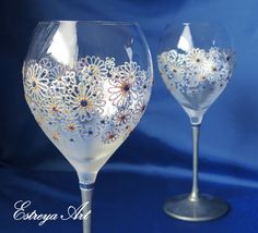"""Set of two hand painted wine glasses """"Silver daisies"""" These beautiful glasses with daisies are in silver, sapphire blue with a hint of gold. They are unique and perfect present for weddings, anniversaries, birthdays, special occasions or just for romantic /special dinners. According to the Anniversary Symbol, the 5th Wedding Anniversary flower is the Daisy. The reason the daisy is the flower chosen to represent the fifth anniversary is because of its symbolic structure. Each of the dais..."""