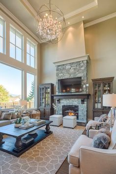 Large living room with two story windows, gorgeous lighting, large area rug, stone fireplace | Clay Construction Inc.
