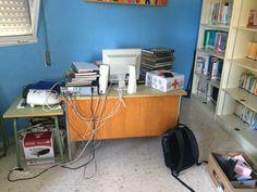 Libros sin etiquetar y cables por todos lados y ordenador obsoleto