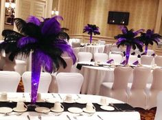 Glass pilsners filled with purple jelly balls and LED lights topped with purple and black ostrich feathers. Doristhefloristt.com