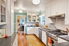White cabinets, white subway tile, blue paint, yellow accents. Would just change the counter color to a little lighter