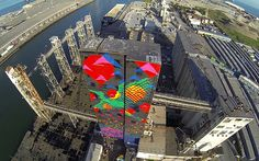 Bayview Rise Pier 92, San Francisco, California, USA, 2014  Bayview Rise is an illuminated mural on the grain elevator and silos of Port Pier 92, at the north entry to San Francisco's Bayview Neighborhood. Growing out of a horizon line is a pattern inspired by native islais cherry plants overlaid onto a field of shorebirds rising from the water. Soaring above is a heron, alluding to nearby Heron's Head Park, a nearby environmental restoration project by the Port. The cow references historic…