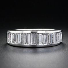 A band of shimmering bright white baguette diamonds beam across the top half of this sleek and streamlined platinum band ring. This timeless, classic wedding band looks great on its own or as a companion to a diamond solitaire.
