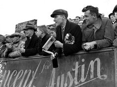 1938: Spectators, one holding a football rattle, at the front of the terraces at a football match.