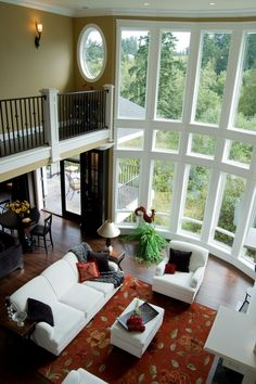 Overhead view of rounded living room featuring dark hardwood flooring, red floral rug, and white furniture set. Full height two story windows illuminate the entire space.
