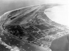 Taken from the radio-gunners compartment, the airstrip and various maintenance facilities on Kwajalein can be seen. Many small boats can also be seen just off the docks for the maintenance work area. Photograph: U.S. Marine Corps (Courtesy of William A. Kehr)