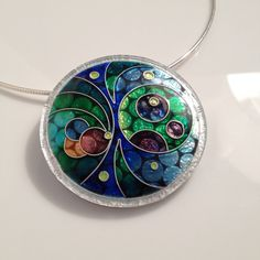 Large cloisonne enamel in an innovative lasercut lucite and silver leaf setting.