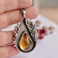 A lovely roll printed leaf serves as the backdrop of this handmade 925 silver pendant. A beautiful natural high grade citrine gemstone nests inside a fine silver bezel and is flanked by hand cast barley, a silver feather, 18 carat gold granules and silver granules. I oxidized the