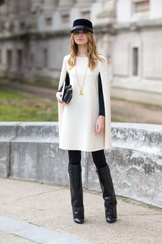 Beautiful white cape coat with long gold necklace and tall black boots