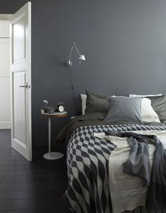 Charming Small Men Bedroom Design Ideas Featuring Gray Wall And White Varnished Wooden Door And White Varnished Wooden Small Table Along With Black Gray Modern Pattern Bed Cover As Well As White Pillow And Gary Pillow As Well As White Fabric Blanket As Well As Black Laminated Floor