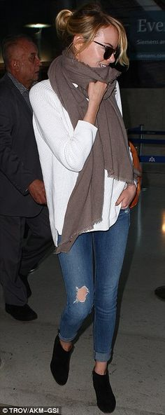 Effortlessly chic: The actress was casual in a simple ensemble of a white blouse, distressed denim jeans, brown scarf, and black boots