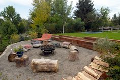 One tier holds this fire pit and casual seating area. Kristina salvaged the seating from a giant tree that was cut down in the neighborhood. An expansive lawn with an inground trampoline sits above this tier,