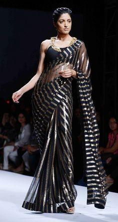 Jesse Randhawa for designer Reynu Tandon in a black & gold saree, with brilliant neckline at Wills Lifestyle India Fashion Week, via Trendy Sarees, Stylish Sarees, Fancy Sarees, Indian Dresses, Indian Outfits, Designer Saree Blouses, Anarkali, Lehenga, Meneses