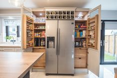 View of pantry and fridge in grey and inky blue contemporary painted Kitchen by Newhaven Kitchens.