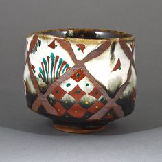 Tomoo Hamada: Tea bowl, stoneware, layered brown and white glazes with wax resist crisscross pattern revealing body beneath, decorated with Okinawa overglaze enamels in red, green and yellow.