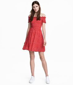 Red dotted. Short, off-the-shoulder dress in crinkled, woven viscose with smocking at top. Short sleeves, seam at waist, and gently flared, lined skirt.