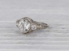 Antique Art Deco engagement ring made in platinum and centered with a GIA certified 1.61 old European cut diamond with H color and VS2 clarity. Circa 1923 Beautiful Art Deco setting that emphasizes the striking old European cut diamond. Old European cut diamonds feature a warmth that newer stones often lack. The cut was the prevailing style from the 1890s to the 1930s. Learn more about Art Deco era engagement rings. Diamond and gold mining has caused devastation in areas such as Africa…