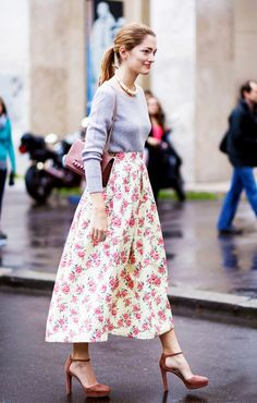 A gray sweater is paired with a floral midi skirt, suede ankle-strap heels, a Valentino bag, and a statement choker