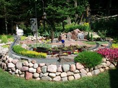Awesome outdoor model train layout that incorporates sedums, sempervivum and jovibarba succulent plants.