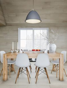 Create an updated coastal style that feels minimalist, but cozy. The key is lots of pieces, but the big elements - oak-colored floors, a frame-in table, plus chairs with dowel bases - are white, ash or beech colored. Light the room up with a graphite pendant lamp and candles.