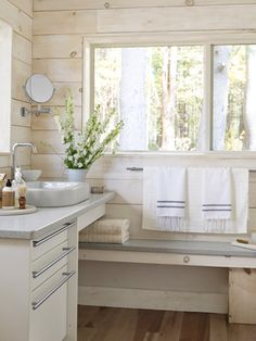 Wood-Paneled Bathroom - The homeowner of this Massachusetts cabin relied on Green Demolition for the guest bathroom's cabinets, as well as its Corian countertops.  The striped-cotton Turkish towels are by Scents and Feel.