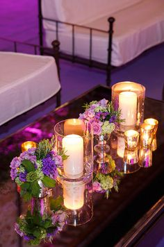 Mirrored tabletops reflect glass hurricanes, votives and small floral arrangmenets with fresh purple blooms.