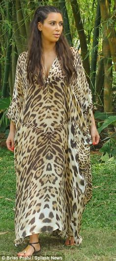 Showing off her wild side: Kim was also seen in a leopard print kaftan and had huge frizzy hair