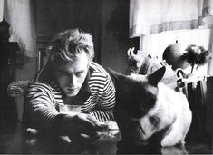 James Dean with Siamese cat named Louis. The cat was owned by Beulah and Sanford Roth. The photo was taken at the Roth's Hollywood residence, 1955.