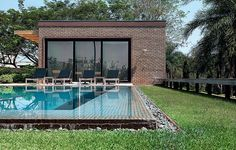 """A piscina retangular tem vista para o campo de golfe do condomínio. """"O detalhe de escoamento de água, como uma borda infinita, passa a sensa..."""