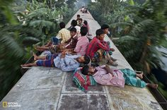 Bangladeshis sleep on the roof of a moving train as they rush home to their respective villages to be with their families, in Dhaka, Bangladesh.