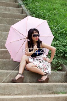 attractive female with umbrella on steps. -
