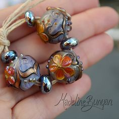 Lilac and Orange shimmer Flowers rounds Lampwork by MadelineBunyan