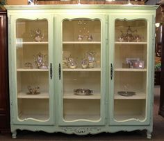 Large French country painted bookcase or display cabinet with 3 glass doors, 3 fixed interior shelves.  Cabinet is painted green with white interior. #OnTheShowroomFloor #French #Country #FrenchCountry #Bookcase #Display #Cabinet #Glass #Doors #Dining #Living #Kitchen #Entry #Foyer #Office #Library #Study #Furniture #Painted #StillGoode