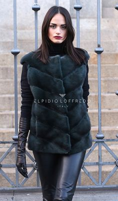 Female Mink Vest with whole skins. Made in Italy. Skins Quality: KOPENHAGEN FUR PLATINUM; Color: Green – Blue; Closure: With hooks; Collar: Plat; Lining: 100% Satin; Lining Color: Monocolor; Length: 65 cm;