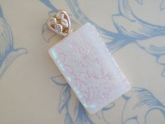 Lace and Love Dichroic Glass Pendant  $30.00  This pendant features white fused glass with a beautiful dichroic silver lace overlay. All topped off with a heart shaped bail large enough to accommodate a ribbon, cord or chain. The ultimate of understated elegance.    Each piece is is kiln fired and annealed for strength and durability. No two are alike and you won't find another on Etsy anywhere. Dichroic glass was hand etched by the artist.
