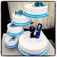5 tier wedding cake with blue roses and bride n groom