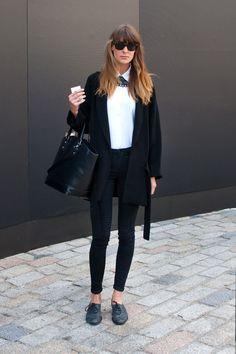 Coggles London Street Style with grey flats, black skinny jeans, white shirt, black oversized cardigan, oversized black leather bag and black sunglasses.