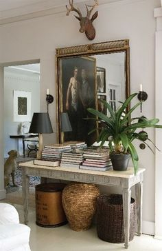 Antique table styled with an antique mirror, books, orchid, baskets, and paper mache deer antlers - Home Decor Details