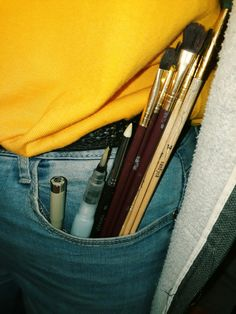 someone with brushes and pens in their pocket, blue, brown, yellow, white