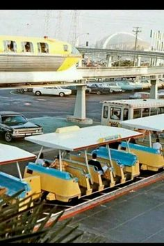 Gotta love that coloring | Vintage photo of the Disneyland parking lot and shuttles and the Monorail above. (This is where they built California Adventure).