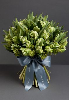 Green leaves and white parrot tulips make an elegant bouquet