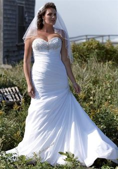 Gown features beading and ruched bodice.  Silhouette: Fit-N-Flare  Neckline: Strapless, Sweetheart  Waist: Dropped  Gown Length: Floor  Train Style: Attached  Train Length: Chapel  Fabric: Taffeta  Embellishments: Beading, Embroidery  Color: White or Ivory  Size: 16W - 26W  Price: $, $$