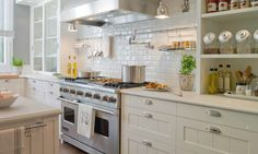 Beautiful kitchen with creamy white ivory kitchen cabinets, light gray honed quartz countertops, subway tiles backsplash, pot filler, open shelves, spice canisters and charcoal gray walls paint color.