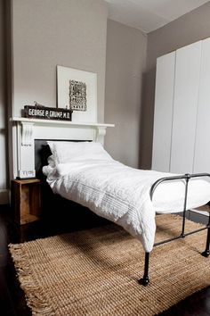 Twin metal bed positioned in front of a traditional white fireplace in a gray bedroom.