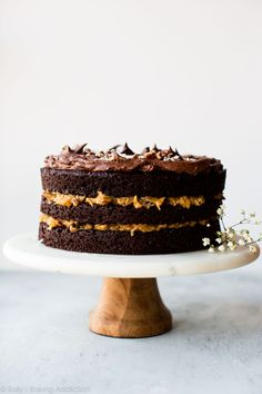 Moist and decadent German chocolate cake with coconut pecan filling and chocolate frosting on top! Recipe on sallysbakingaddiction.com