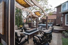 """This luxurious lounge is gathered around a large gas fire table and lit with LED-backlit slate panels that are curved to match the curvy aerial beams.  From """"Decked Out"""" project """"The Stone Deck"""". Deck design by Paul Lafrance Design."""