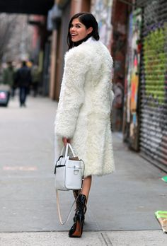 EMILY WEISS, INTO THE GLOSS, NYC  wearing a white furry coat, studded ALAIA shoes and a white Reed Krakoff bag