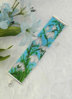 This pretty Bead Loom Bracelet features Snowdrop flowers. Snowdrop flowers are widely found in northern Europe and are sometimes called the spring snowflake. I made this 6 1/2 inch bracelet with 11/0 round seed beads and finished it off with a Silver plated lobster claw clasp with a 3