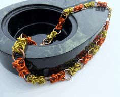 This lovely fall choker necklace is fit for any man or woman wanting to show off their fall spirit. It features anodized aluminum jumprings that are a light leafy brown color, bright orange, and lemon