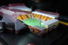 Valley Parade Stadia Model - Bradford City FC @ sportsstadiaart.co.uk  HAND MADE MODEL WITH WORKING FLOODLIGHTS OF THE VALLEY PARADE STADIUM, HOME OF BRADFORD CITY FC. Each model comes on a black wooden frame with a clear plastic display cover. Lights are operated via a slide switch on the underside of the model. Lights operated by 3x AAA batteries(included) Model measures 23.5cm x 21.5cm. Click on the Personalise tab above to add a name or message on the stadium model.